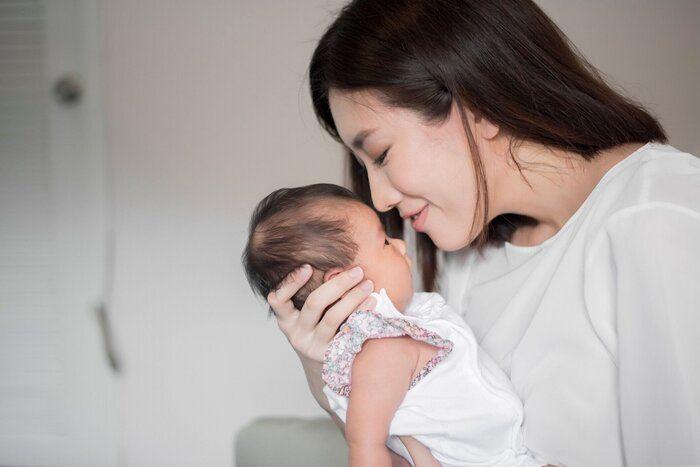 彼女の腕の中に生まれたばかりの赤ちゃんを抱いている美しい女性