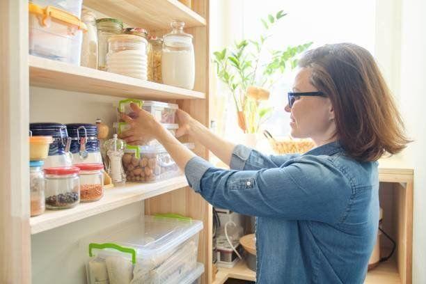 調理のための製品と木製のパントリーのインテリア。棚から台所用品や食べ物を取る大人の女性