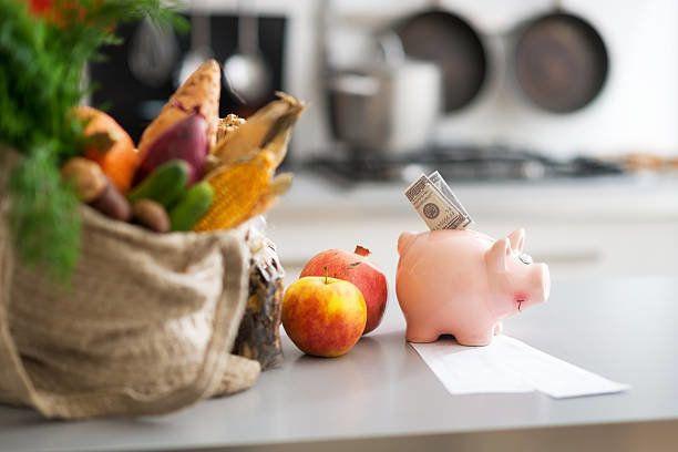 お金でピギー銀行および購入されたアイテムにテーブルを配しております。のクローズアップ