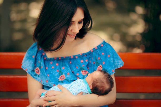 屋外の肖像画で新生児を保持する幸せな母親