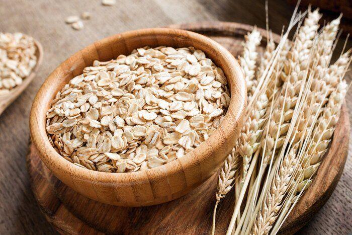 転がされたオートムギまたはオート麦フレーク、木製の背景に黄金の小麦の穂。