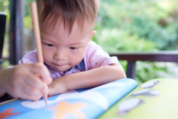 かわいいアジア 2 歳幼児男の子を書く/鉛筆、未就学児の宿題で