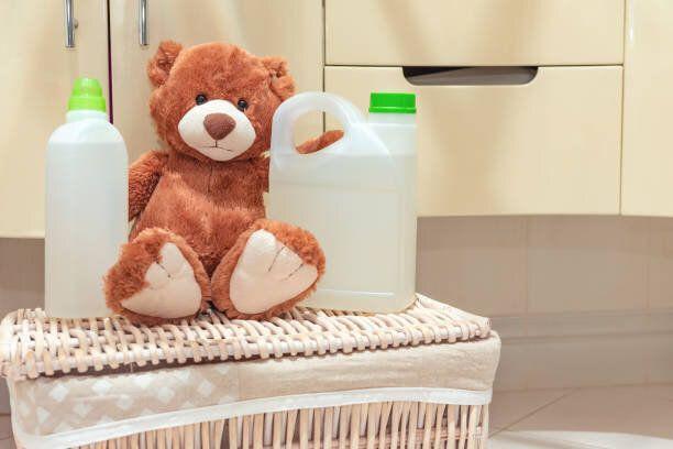 ぬいぐるみのテディベアは、洗剤とすすいでの援助の隣のバスルームの洗濯かごに座っています。ホームランドリー