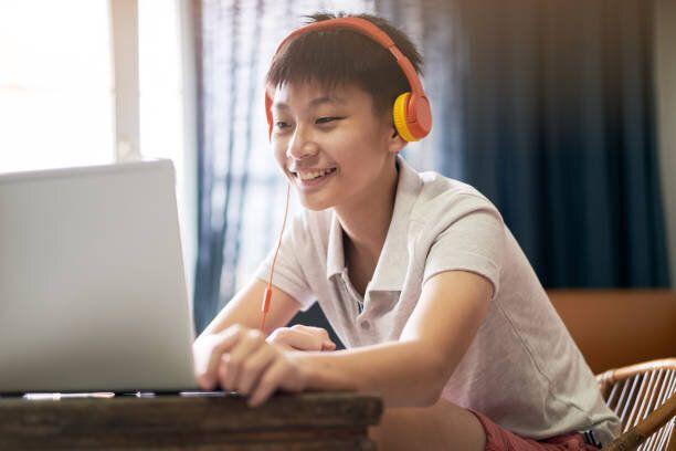 ヘッドセットを身に着けている自宅でオンラインレッスンを受けるアジアの10代の少年