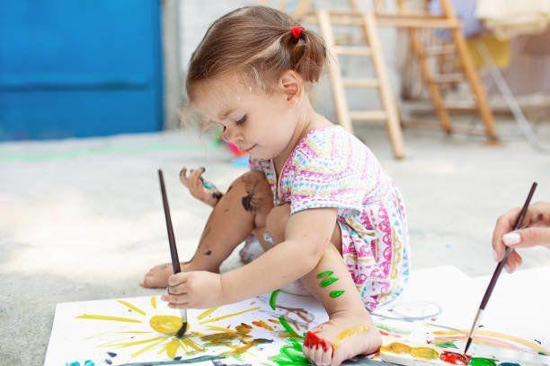 かわいい白人少女紙で裏庭で絵を楽しんで、水の色やアート ブラシです。選択と集中