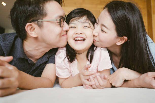 アジアの両親は両方の頬に彼らの小さな娘にキス。家族の肖像画。