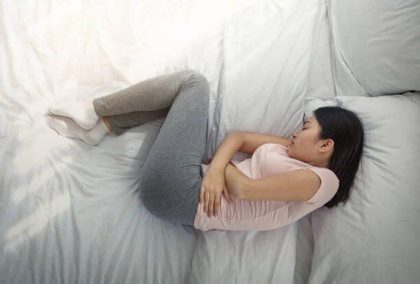 ベッドの屋内で痛みを抱く韓国の女の子の睡眠, トップビュー
