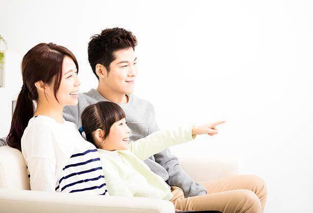 幸せな魅力的な若い家族ご覧になりながら、テレビ