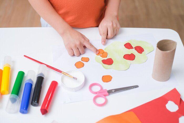 小さな3歳の幼児の男の子のトップビューは、家庭で芸術を行う接着剤を使用して楽しむ、幼児のための楽しい紙や接着剤の工芸品、子供のアートプロジェクト