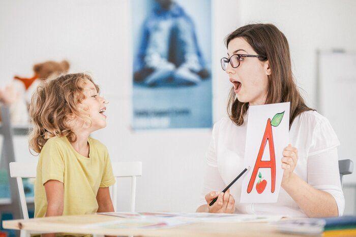 言語聴覚士 ' 絵手紙と小道具を使用して正しい発音で子供と作業します。