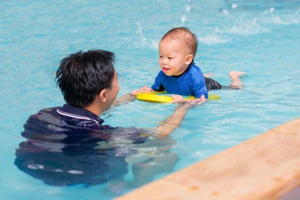 アジアの父は水泳教室に少しのかわいいアジア 18 ヶ月/1 年古い幼児赤ちゃん男の子の子供を取る