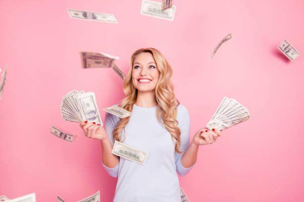 かなり魅力的な肯定的なかわいい成功した幸運な陽気な少女が立っているピンクの背景で隔離の手でたくさんのお金を持っているお金からシャワーの下で肖像画