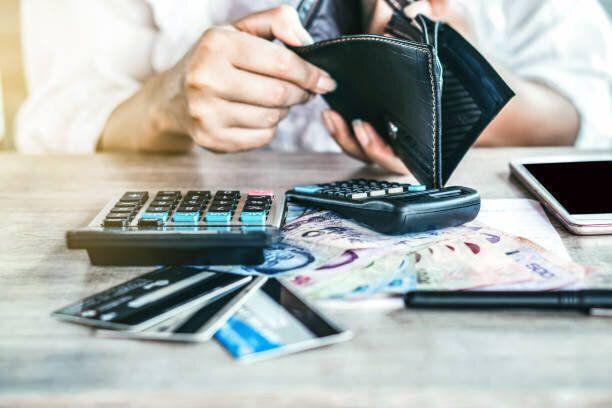 貧しい女性の手オープン空の財布クレジットカードの借金のためのお金を探して