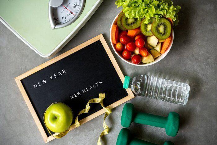 新年の健康のための2021年。 女性ダイエット痩身の減量の背景のためのスポーツ機器のための新鮮な野菜サラダと健康的な食品。